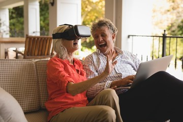 Senior couple using laptop and experiencing VR headset in porch