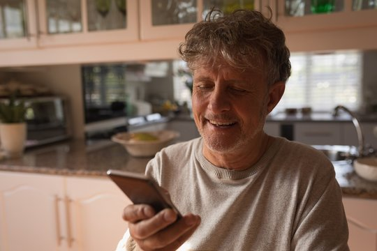 Senior man using mobile phone in the kitchen