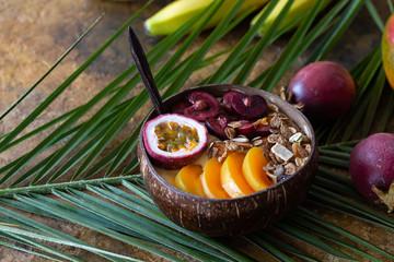 Smoothie bowl with fresh mango, passion fruit black cherry and granola