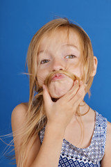fillette blonde 7 ans avec vent dans les cheveux et ventilateur studio