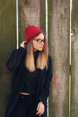 Stylish blond woman in glasses and red warm hat posing outdoors