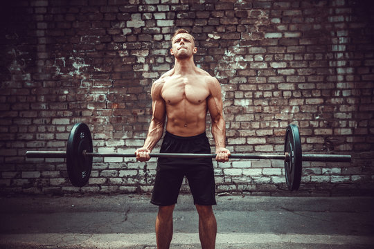 Athletic man working out with a barbell in front of brick wall. Strength and motivation. Outdoor workout. Biceps exercise.