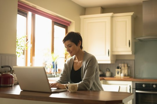 Woman using laptop in the kitchen