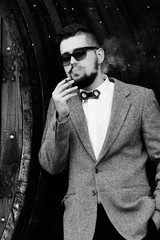 Man smoking. Black and white portrait of handsome young bearded man smoking a cigarette while standing against wood wall