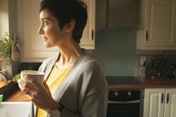 Woman looking away while having coffee in the kitchen