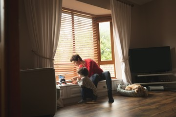 Mother playing with son on window sill in living room