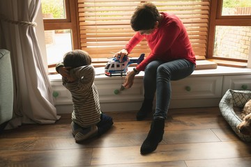 Mother playing with son on window seat in living room