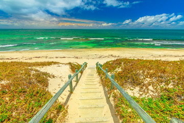 Foto op Canvas Oceanië Wooden stairs for Mettams Pool, North Beach near Perth, Western Australia. Mettam's is a natural rock pool protected by a surrounding reef. Summer season.