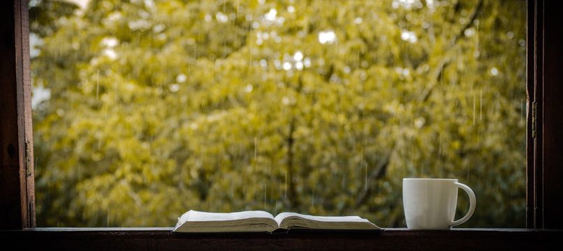 Cozy autumn still life: cup of hot coffee and opened book on vintage windowsill and rain outside. Autumn. Apartment. Rain