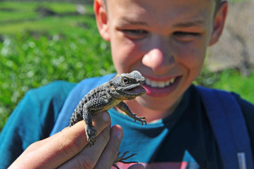 Young happy zoologist holding lizard in hands