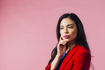 Young woman thinking with hand on face looking off camera, isolated on pink studio background