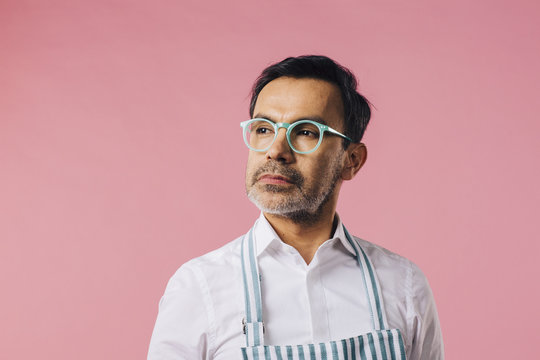 Mature man with blue glasses looking off camera, isolated on pink studio background