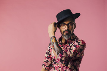 Horizontal portrait of a very cool man with tattoos, tilting his hat, isolated on pink studio background