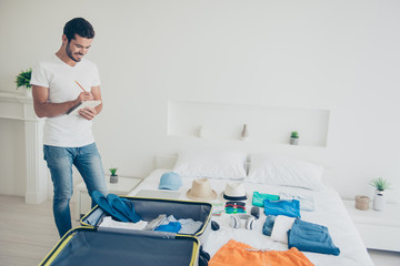 Young attractive handsome bearded smiling brunet man packing stuff to a trip, check list. White interior room