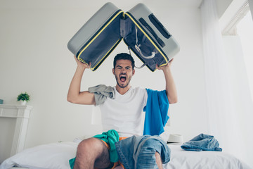 Handsome young bearded brunet evil crazy man wearing white t-shirt, sitting indoors on bed, packing luggage to a trip, journey, holding bag above head, shouting, room in mess