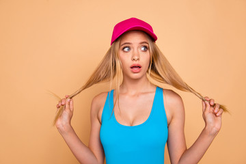 Portrait of young attractive nice cute straight-haired blonde funky girl wearing casual, bright pink cap, tearing, pulling her hair curls. Isolated over beige background