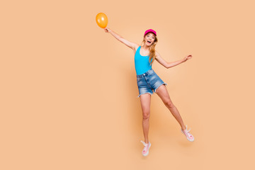 Full length size body portrait of young attractive blonde excited girl wearing casual, jeans shorts, sneakers, bright pink cap, flying away, keeping yellow air baloon. Isolated over beige background