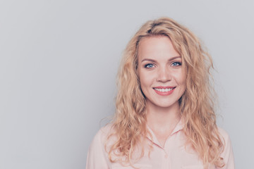 Portrait of young attractive nice cute caucasian smiling curly-haired blonde girl wearing casual shirt. Isolated over grey background