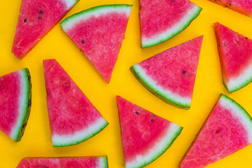 Fresh watermelon slices on the yellow background. Summer fruit concept.