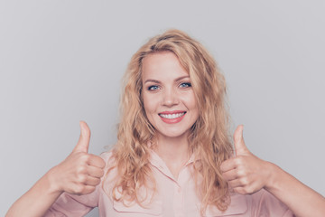 Portrait of attractive cute curly-haired blonde gorgeous pretty girl wearing casual shirt showing two thumbs up signs. Isolated over grey background