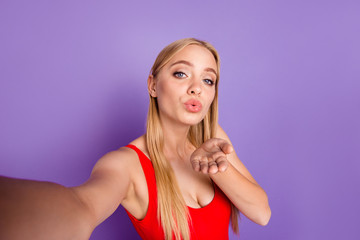 Self portrait of attractive cheerful playful blonde funny gorgeous girl wearing red swim suit sending you air kiss with pouted lips. Isolated over violet pastel background
