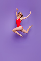 Full-legh portrait of girl in summer glasses jumping high raising her arms up and laughing isolated on purple background