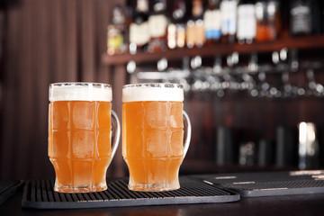 Glasses of tasty beer on bar counter