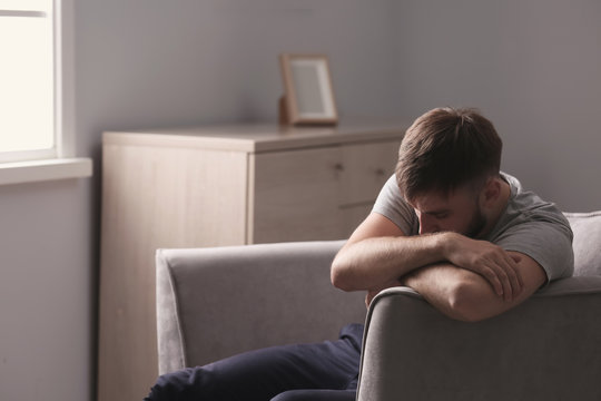 Depressed young man sitting in armchair at home