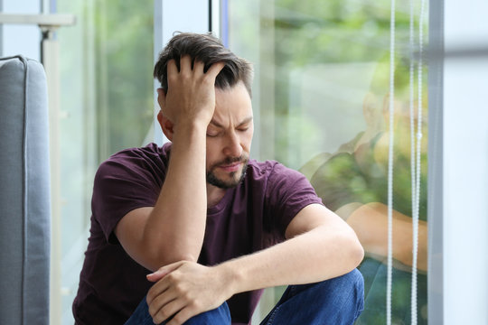 Lonely depressed man near window at home