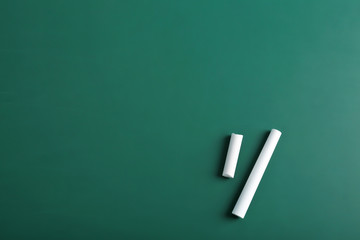 Pieces of chalk on green background, top view