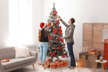Happy young couple decorating Christmas tree together at home