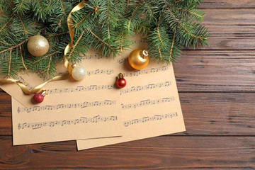 Flat lay composition with Christmas decorations and music sheets on wooden background