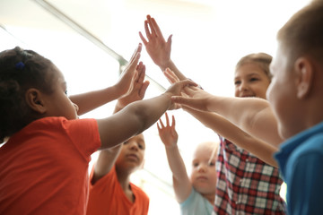 Little children putting their hands together on light background. Unity concept