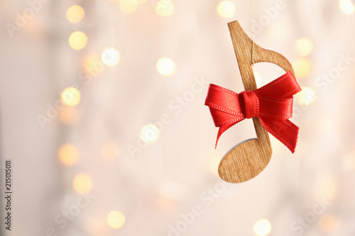 92fa8a097a67e Wooden note with bow against blurred lights. Christmas music concept ...