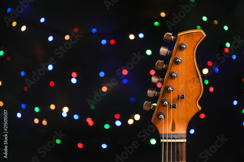 167ec86cad20f Guitar against blurred lights. Christmas music concept