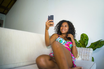 young attractive and beautiful happy black latin American woman taking selfie portrait picture with mobile phone at holidays apartment