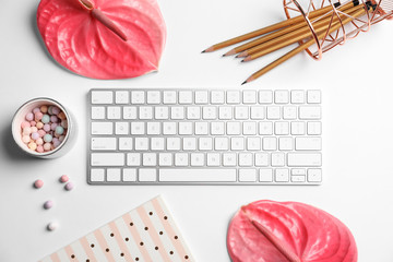 Creative flat lay composition with tropical flowers, stationery and computer keyboard on white background