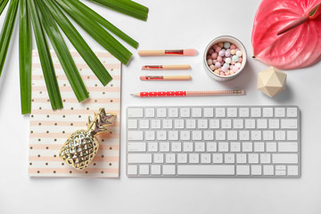 Creative flat lay composition with tropical flower, stationery and computer keyboard on white background