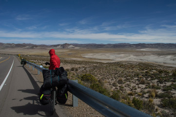 traveler on a bicycle stopped on a highway in Bolivia
