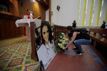 A woman places a bouquet of flowers in front of a picture of Rayneia Gabrielle Lima, a medical student who died in unclear circumstances, during a mass in her honor at the Metropolitan Cathedral in Managua