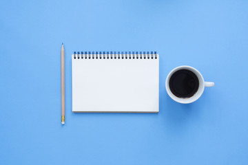 Office desk working space - Flat lay top view mockup of a working space with white blank notebook page, coffee cup on blue pastel background. Pastel blue color background space concept.