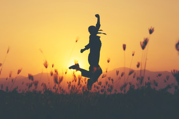 Freedom and sucess - woman happy at meadow . Free cheering girl with arms raised enjoying serene sunset in winning pose with arms stretched.