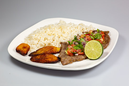 A steak covered in pico de gallo surrounded by plantains and white rice on a white plate. Cuban food.