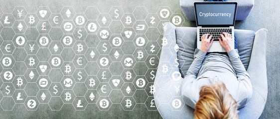 Cryptocurrency theme with man using a laptop in a modern gray chair