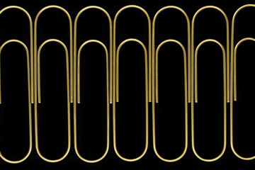 Group of sharp and clear view of golden paperclips standing in line on black background surface