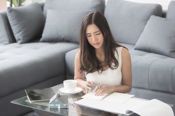 Beautiful Asian girl smiling sitting on the sofa working home design with large sheets the luxury room