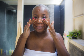 young attractive and happy black african American woman at home bathroom looking on toilet mirror applying face beauty moisturizer gel