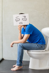man with constipation on toilet