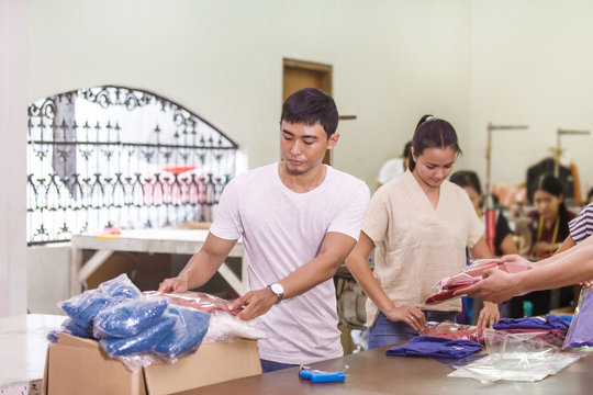workers at textile company stacking their products into a box