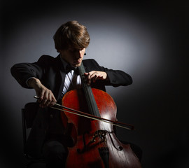 Young man playing the cello. Portrait of the cellist on a dark background.
